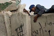 An elderly Palestinian man pauses for rest as he tries to climb over the Cement barrier wall that runs along the East Jerusalem neighborhood of Abu Dis and the West Bank Tuesday Nov.25,2003. Today Palestinians marked the beginning of the Muslim holiday of Eid al-Fitr. (Photo by Heidi Levine/Sipa Press).