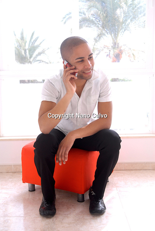 MR Portrait of an elegant mulatto young man in his twenties, talking with his phone in a living room