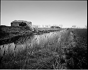 THE ATLANTIC WALL. .pic shows: HOLLAND. BUNKERS NEAR KOUDEKERK ON WALCHEREN TO THE WEST OF MIDDELBURG. THE BUNKERS WERE PART OF THE DEFENCE OF THE SCHELDE RIVER AND THE PORT OF ANTWERP..WORLD WAR TWO ENDED IN EUROPE IN MAY 1945, THIS YEAR SEES THE 60th ANNIVERSARY OF THAT VICTORY..THE ATLANTIC WALL BUILT BY GERMANY IN WORLD WAR 2 STRETCHED FROM NORWAY VIA DENMARK, HOLLAND, BELGIUM AND FRANCE TO THE SPANISH BORDER. THE MAIN CONCENTRATION OF BUNKERS,BLOCKHOUSES AND DEFENCES WERE ALONG THE DUTCH, BELGIAN AND FRENCH COASTAL AREAS MOST UNDER THREAT FROM AN ALLIED INVASION. THE CONSTRUCTION OF THE WALL BEGAN IN 1942 AND CONTINUED UP UNTIL THE JUNE 6th ALLIED INVASION ON D-DAY IN 1944..TENS OF THOUSANDS OF WORKERS AND PRISONERS FROM THE GERMAN OCCUPIED AREAS OF EUROPE WERE EMPLOYED BY THE ORGANISATION TODT NAMED AFTER FRITZ TODT, THE GERMAN ENGINEER WHO DIED IN 1942 (TO BE SUCEEDED BY ALBERT SPEER) IN THE BUILDING WORK. BETWEEN THE RIVERS LOIRE AND DIVES 87,257 WORKERS WERE USED INCLUDING 55,000 FRENCHMEN, 11,500 GERMANS, 4,200 DUTCH, 6.600 BELGIANS, 2,600 NORTH AFRICANS AND SEVERAL THOUSAND FROM EASTERN EUROPE..THE ATLANTIC WALL WAS THE LARGEST BUILDING PROJECT SINCE THE ROMAN EMPIRE. MANY OF THE COLOSSAL GUN BUNKERS AND UNDERGROUND DEFENSIVE CHAMBERS REMAIN. SOME HAVE FALLEN FROM CLIFF TOP POSITIONS WHILE OTHERS ARE PARTLY CONSUMED BY SAND DUNES. THE RAVAGES OF WAR, TEN THOUSAND TON BOMBS AND 60 YEARS OF COASTAL WEATHER HAVE HARDLY AFFECTED THESE LEVIATHAN LIKE STRUCTURES WHICH LOOK LIKELY TO LAST AS LONG AS THE RUINS OF ANCIENT ROME. A FITTING REMINDER OF A WORLD THAT COULD HAVE BEEN FROM 60 YEARS AGO..COPYRIGHT PHOTOGRAPH BY BRIAN HARRIS  © 2005.07808-579804