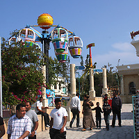Scenes from Tunisia's resort area, El Kantouai. Amusement park with rides and visitors
