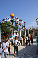Scenes from Tunisia's resort area, El Kantouai. Amusement park with rides and visitors