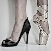 Legs of a ballerina with a black high heel shoe in one feet and a pointe ballet shoe in the other.