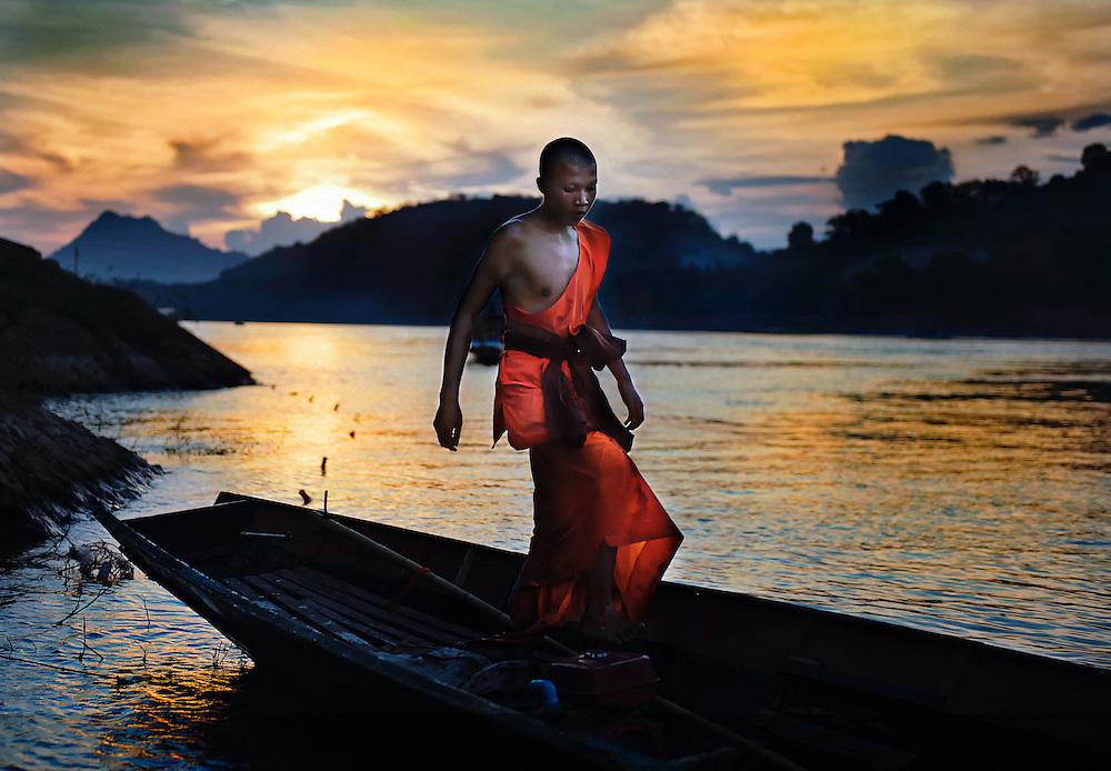 A novice on the Mekong river at sunset, Luang Prabang, Laos.