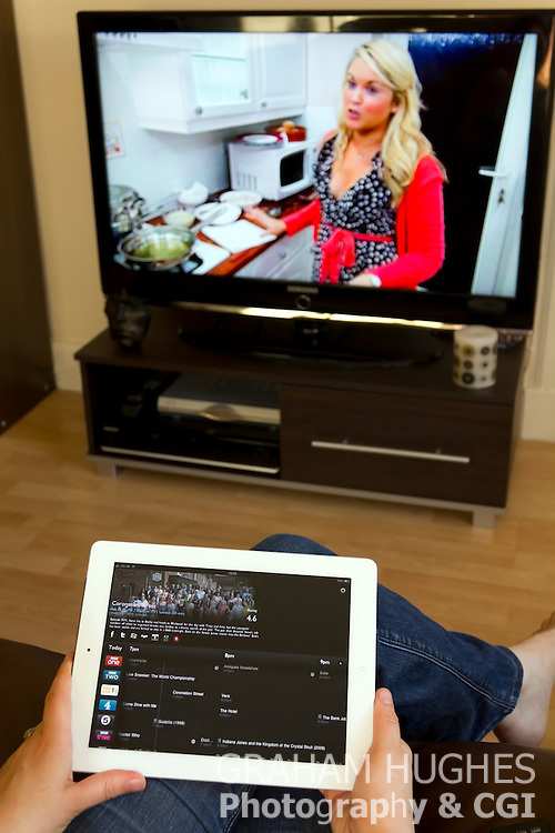 Woman sat on couch searching TV listings on iPad 2 App.