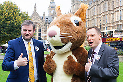 """Nature campaigners accompanied by a  giant red squirrel, Bob, urge MPs to """"Vote For Bob"""" during a photocall outside Parliament. Their aim is to get MPs to support nature in Britain. PICTURED:  MPs Andrew Stephenson, left, and Jason McCartney pose with Bob the red squirrel."""