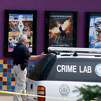 """Police continue to investigate at the movie theater where 12 people were shot last Friday as a showing of """"Batman"""" (center poster in background) in Aurora, Colorado July 23, 2012. REUTERS/Rick Wilking (UNITED STATES)"""
