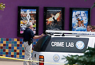"Police continue to investigate at the movie theater where 12 people were shot last Friday as a showing of ""Batman"" (center poster in background) in Aurora, Colorado July 23, 2012. REUTERS/Rick Wilking (UNITED STATES)"