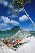 Bora Bora, Tahiti: woman in hammock on beach at Bora Bora Lagoon Resort.