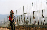 """A security man who does not want to be identified by name guards with a Uzi sub machine gun   early morning Friday November 22,2002 by the electric barbed wire fence along the village Israeli Arab village of Salem near the West Bank city of Jenin . The guard say's that it is either """"them or us""""Aprox. 1.5 kilometers of barbed wire fence has been erected so far.The fence Israel claims will prevent Palestinian suicide bombers will run along the West Bank. The barrier is expected to eventually run the full length of the 300-kilometer (180-mile) frontier between Israel and the West Bank, which it occupied in the 1967 Mideast war.(Photo by Heidi Levine/Sipa Press)."""