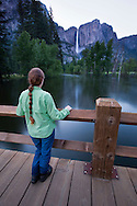 A woman looks over a flooded Merced River at Yosemite Falls from Swinging Bridge in Yosemite valley - Yosemite National Park, California