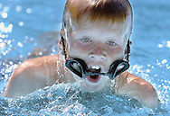 Scooter Gill, 9, maintains his stroke despite loosing his goggles during the 50-meter butterfly of the Pines versus Golf & Tennis Swim Meet at Teton Pines.