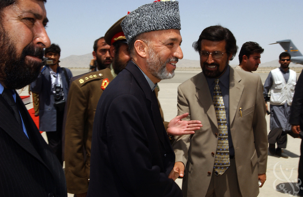 Interim Afghan president Hamid Karzai (c) is greeted on his arrival by local leaders, including Kandahar governor Gul Agha Sherzai (l) May 04, 2002 in the southern Afghan city of Kandahar. The visit by Karzai to the city, his first since assuming power, is significant because of the city's history as a former Taliban stronghold.