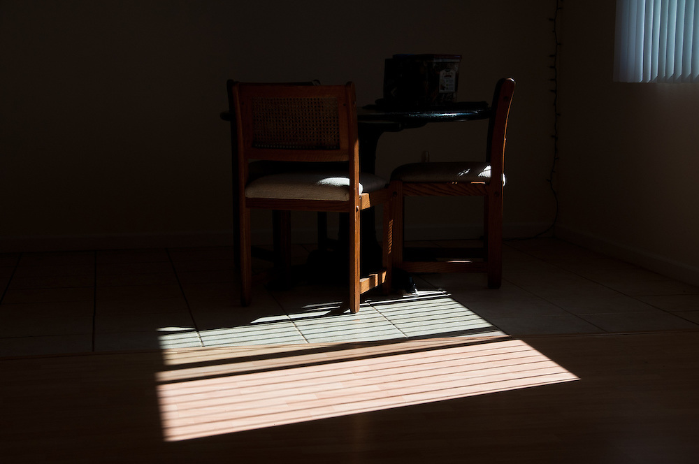 Outside lights cast stong shadows and partially illuminate the simple furniture. Old house in Toumbstone, Arizona.