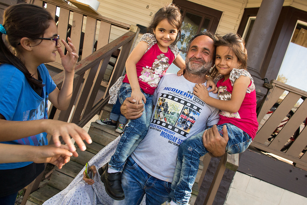 Windsor, Ontario ---2015-09-10--- Walid Jawish holds his six year old twin girls Miral(L) and Mirna at their new home in Windsor, Ontario September 10, 2015. The family of 9 arrived in Canada as refugees in June, 4 years after fleeing the violence in Syria.<br /> GEOFF ROBINS The Globe and Mail