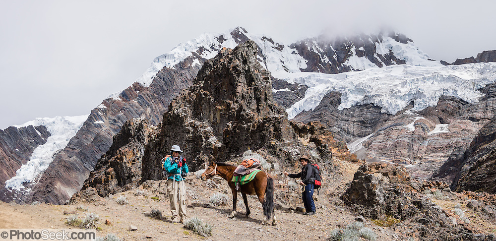 Trekkers with horse rest at Yanacon/Yanajanca col (15,100 feet or 4610 m) below glaciers of Pucajirca Norte (6046 m). Day 5 of 10 days trekking around Alpamayo in Huascaran National Park (UNESCO World Heritage Site), Cordillera Blanca, Andes Mountains, Peru, South America. This panorama was stitched from 2 overlapping photos.