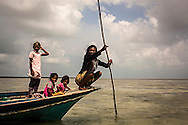 A Bajau woman controls the depth of the sea at low tide