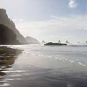 Pacific Ocean waves have eroded seastack rocks from high bluffs and created a sandy beach, south of Cape Meares on the Oregon coast, USA. Clouds streak across the blue sky. Panorama stitched from 2 overlapping images.
