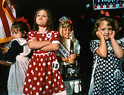 Young girls display various reactions to the results just announced during a Little Miss 4th of July contest.