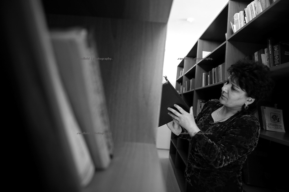 "A librarian orders books in the new built library in Shushi.  This image is part of the photoproject ""The Twentieth Spring"", a portrait of caucasian town Shushi 20 years after its so called ""Liberation"" by armenian fighters. In its more than two centuries old history Shushi was ruled by different powers like armeniens, persians, russian or aseris. In 1991 a fierce battle for Karabakhs independence from Azerbaijan began. During the breakdown of Sowjet Union armenians didn´t want to stay within the Republic of Azerbaijan anymore. 1992 armenians manage to takeover ""ancient armenian Shushi"" and pushed out remained aseris forces which had operate a rocket base there. Since then Shushi became an ""armenian town"" again. Today, 20 yeras after statement of Karabakhs independence Shushi tries to find it´s opportunities for it´s future. The less populated town is still affected by devastation and ruins by it´s violent history. Life is mostly a daily struggle for the inhabitants to get expenses covered, caused by a lack of jobs and almost no perspective for a sustainable economic development. Shushi depends on donations by diaspora armenians. On the other hand those donations have made it possible to rebuild a cultural centre, recover new asphalt roads and other infrastructure. 20 years after Shushis fall into armenian hands Babies get born and people won´t never be under aseris rule again. The bloody early 1990´s civil war has moved into the trenches of the frontline 20 kilometer away from Shushi where it stuck since 1994. The karabakh conflict is still not solved and could turn to an open war every day. Nonetheless life goes on on the south caucasian rocky tip above mountainious region of Karabakh where Shushi enthrones ever since centuries."
