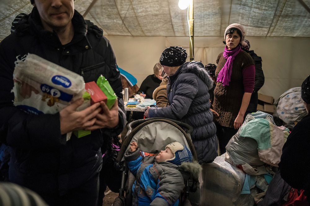 People displaced by fighting between pro-Russia rebels and Ukrainian forces in Eastern Ukraine inside a tent where they can receive free second-hand clothes, a service offered at a processing center for internally displaced people located at the train station on Monday, February 9, 2015 in Slovyansk, Ukraine.