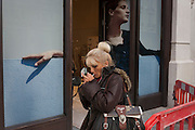 A woman lights a cigarette beneath a retail poster in central London.