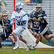 John Kemp Goalie #1 stands ready as Duke attack Jordan Wolf #31 drive son goal. The third-ranked Fighting Irish defeated sixth-ranked Duke, 13-5, in men's lacrosse action on a snowy Saturday afternoon at Koskinen Stadium in Durham, N.C.