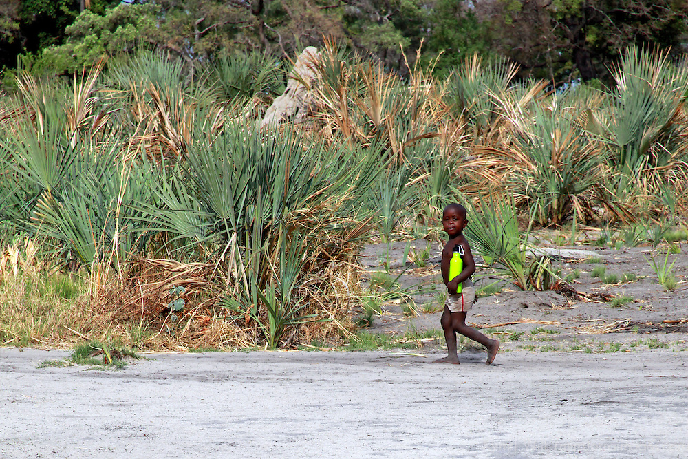 Africa, Botswana, Okavango Delta. Small boy walking in Okavango Delta village carrying a water bottle.