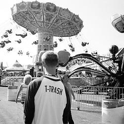 A man walks down the state fair midway wearing a T-Trash tee shirt