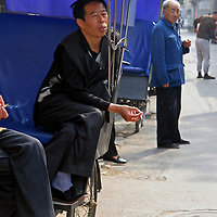 Asia, China, Beijing. Rickshaw drivers take a smoking break between pedaling tourists through Beijing's hutongs.