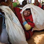 A woman clowns for the camera in a food distribution queue at the Mbera refugee camp for Malian refugees in Mauritania on 1 March 2013.