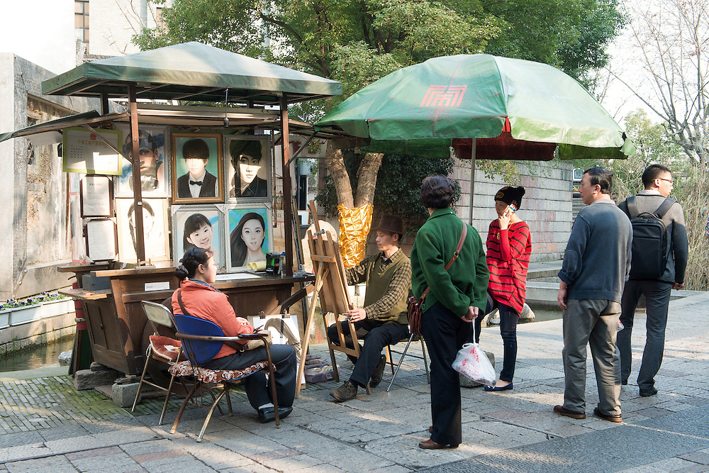 A street artist doing a portrait drawing with onlookers watching