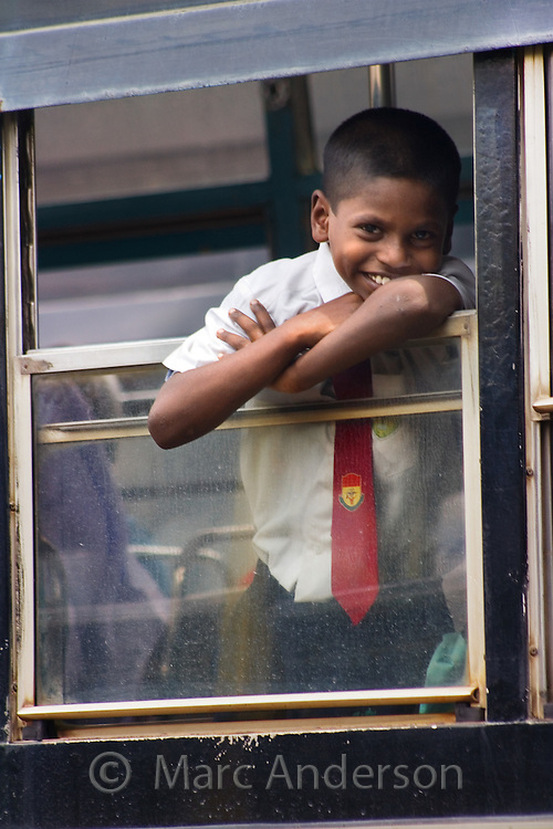 An Indian school boy looking out of a bus window in Malaysia.