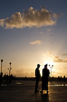 A couple of men share a conversation on the plaza in Essaouira, Morocco.