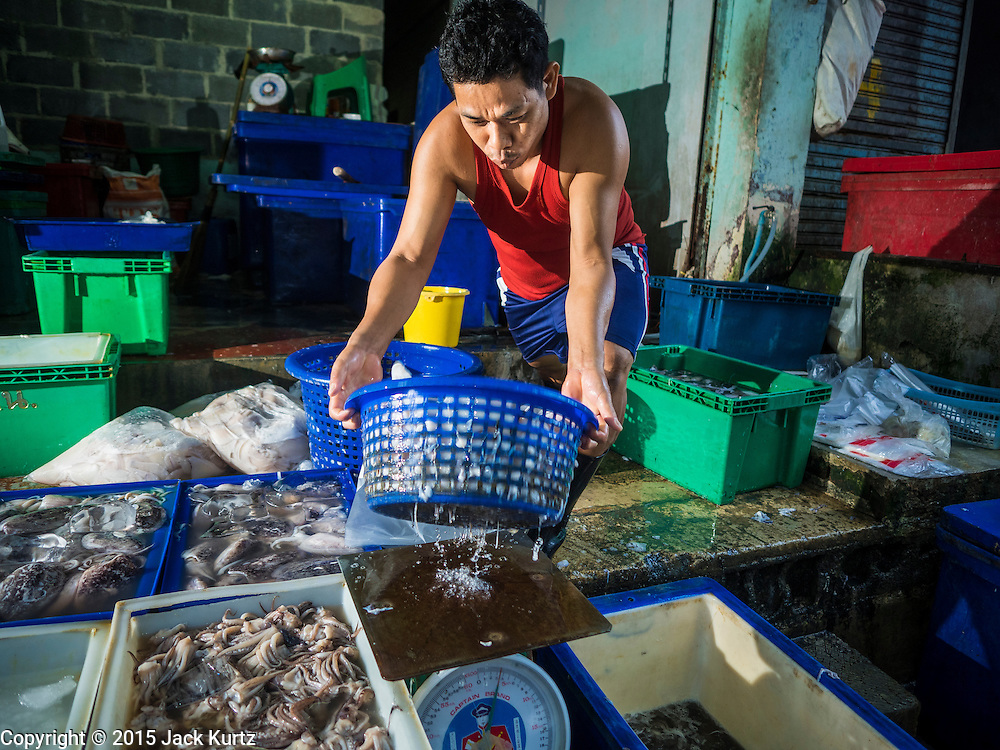 14 AUGUST 2015 - BANGKOK, THAILAND:  A man packages fresh squid in Saphan Pla fish market in Bangkok. Saphan Pla fish market is the wholesale fish market that serves Bangkok. Most of the fish sold in Saphan Pla is farmed raised fresh water fish. The market is open 24 hours but it's busiest in the middle of the night and then again from about 7.30 until 11 in the morning.       PHOTO BY JACK KURTZ
