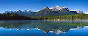 """Herbert Lake reflects peaks in Banff National Park, Alberta, Canada. Banff is part of the Canadian Rocky Mountain Parks World Heritage Site declared by UNESCO in 1984. Panorama stitched from 3 images shot on film. Published on the cover of John Steel Rail Tours corporate brochure 2006, www.johnsteel.com. Published in """"Light Travel: Photography on the Go"""" book by Tom Dempsey 2009, 2010."""