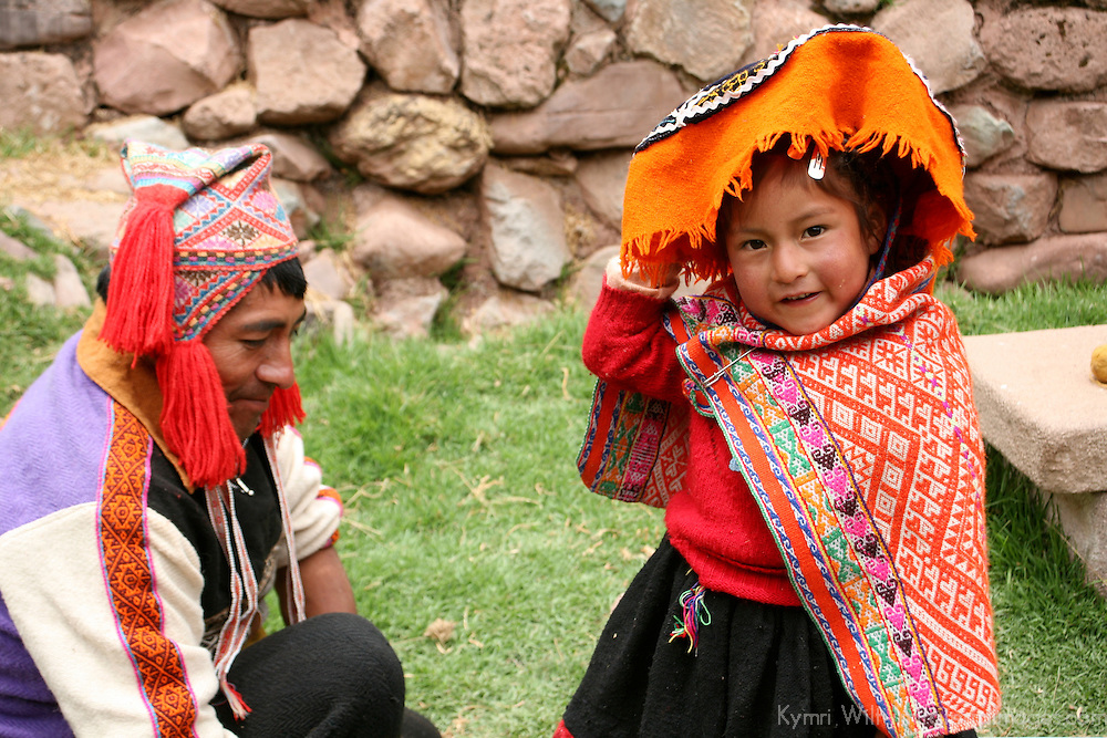 Americas, South America, Peru, Cusco. A young girl and her father at Awana Kancha in the Sacred Valley.