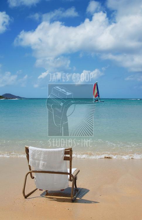 An empty chair on the beach facing outward to the deep blue seascape.