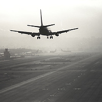Jet airline landing in the overcast at Lindberg Field, San Diego, CA. Shot from behind, low angle.