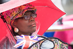 Trafalgar Square, London, June 12th 2016. Rain greets Londoners and visitors to the capital's Trafalgar Square as the Mayor hosts a Patron's Lunch in celebration of The Queen's 90th birthday. PICTURED: A woman watches the performers on stage.