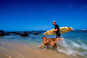 Surfer running with dog on the beach