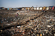 A man crosses a severely polluted river in the suburb of Agbogbloshie, in Accra, Ghana. When the rains come much of this waste will be washed to the sea.