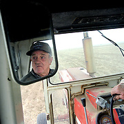 A farmer plows his Colorado field in an old tractor