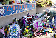 """A woman places a """"Peace"""" sign at a memorial outside the offices of congresswoman Gabrielle Giffords in Tucson, Arizona January 9, 2011. Charges against the suspect in a shooting rampage that wounded Giffords and killed six others were expected on January 9, FBI Director Robert Mueller said.  REUTERS/Rick Wilking (UNITED STATES)"""