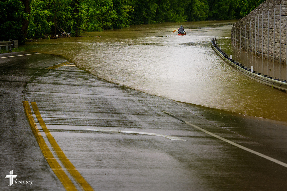 A man paddles to his house down a flooded road on Wednesday, May 4, 2017, in Eureka, Mo. LCMS Communications/Erik M. Lunsford