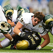 SHOT 9/1/2007 - Colorado State's Jesse Nading (#59, DE) loses  his helmet while tackling Colorado's Demetrius Sumler (#8, TB) with the help of teammates during the first half of the Rocky Mountain Showdown Saturday September 1, 2007 at Invesco Field in Denver, Co. The University of Colorado won the Centennial Cup with a 31-28 overtime victory in the game. Colorado and Colorado State have met 78 times in their histories, but the first 69 took place on their respective campuses. The Colorado Buffaloes are in the Big 12 Conference, while the Colorado State Rams compete in the Mountain West Conference..(Photo by Marc Piscotty © 2007)