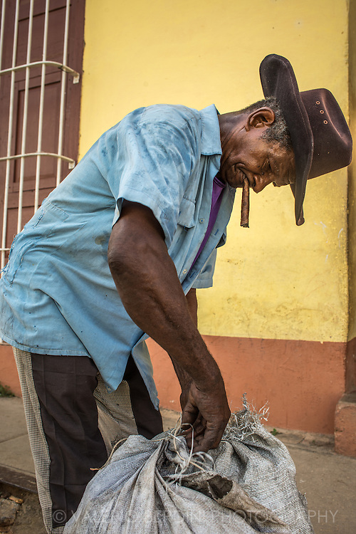 A man with his cigar packs his belonging in a street in Trinidad, Cuba.