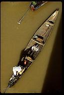 Man motors home in dugout canoe w/ fish catch on Rio Acre; view from bridge at Rio Branco, Acre. Brazil