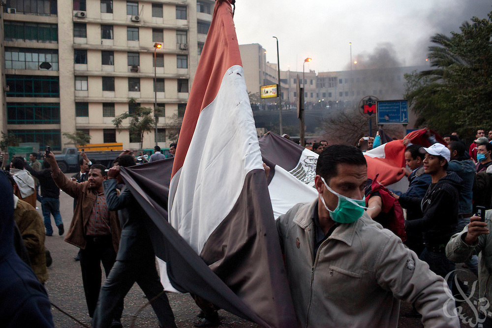 Egyptian protesters march with a flag down Ramsis street during massive and unprecedented demonstrations January 28, 2011 across Cairo, Egypt . The protests, inspired by the recent revolution in Tunisia, have struck a chord with Egypt's population, tired of inflation, high unemployment and alleged corruption within the Mubarak government..Slug: Egypt.Credit: Scott Nelson for the New York Times