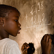 A girl solves a math problem during class at the Kabiline I Primary school in the village of Kabiline, Senegal on Wednesday June 13, 2007.