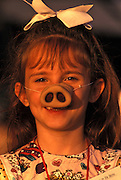 Image of a young girl wearing a pig nose at a barbecue in Lafayette, Louisiana, American South, model released